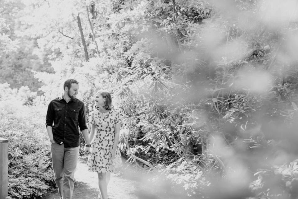 Black and white candid photo of couple walking hand in hand through the woods