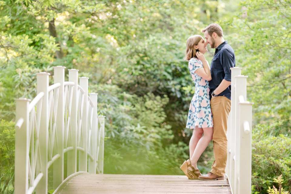 Couple facing one another, nose to nose, smiling, standing on top of a bridge in park