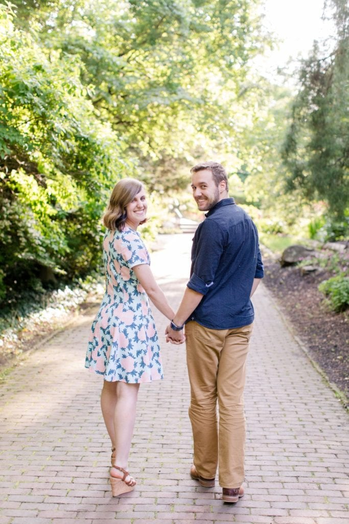 full length photo of couple from behind, walking away from camera, looking back and smiling
