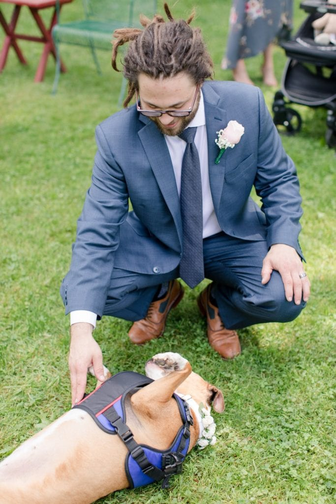 The groom plays with one of his dogs. Floral dog collar by Luna Blu Creates