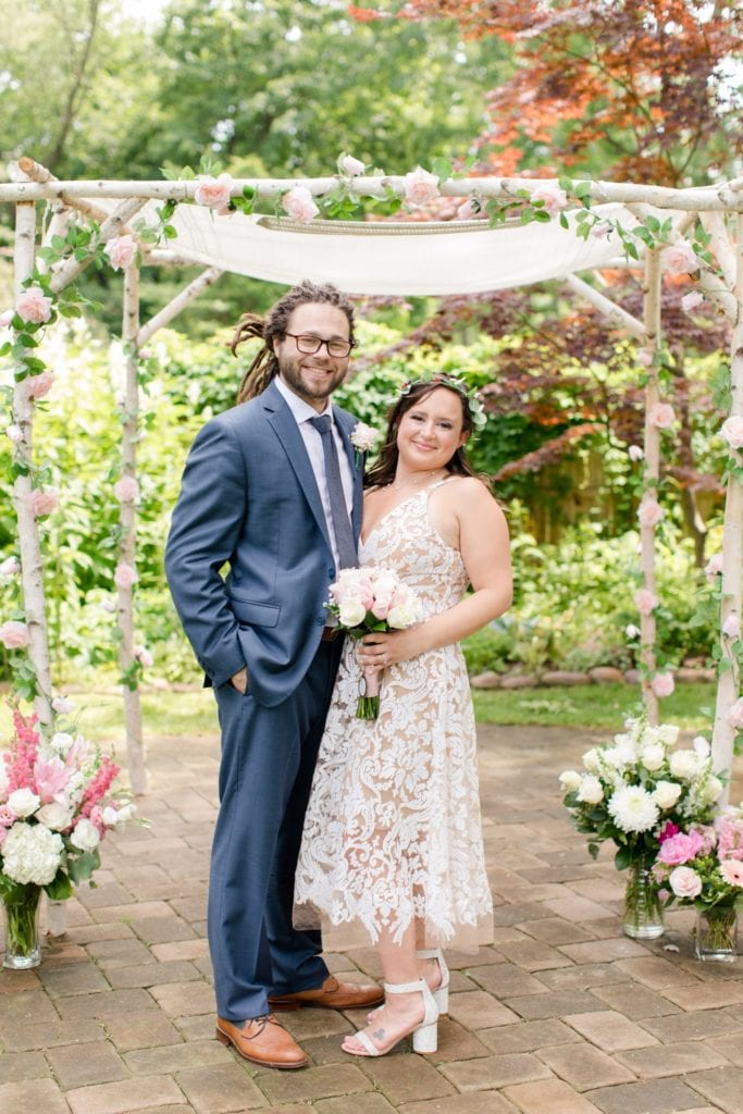 A full length formal portrait of the bride and groom outside in front of their white birch chuppah