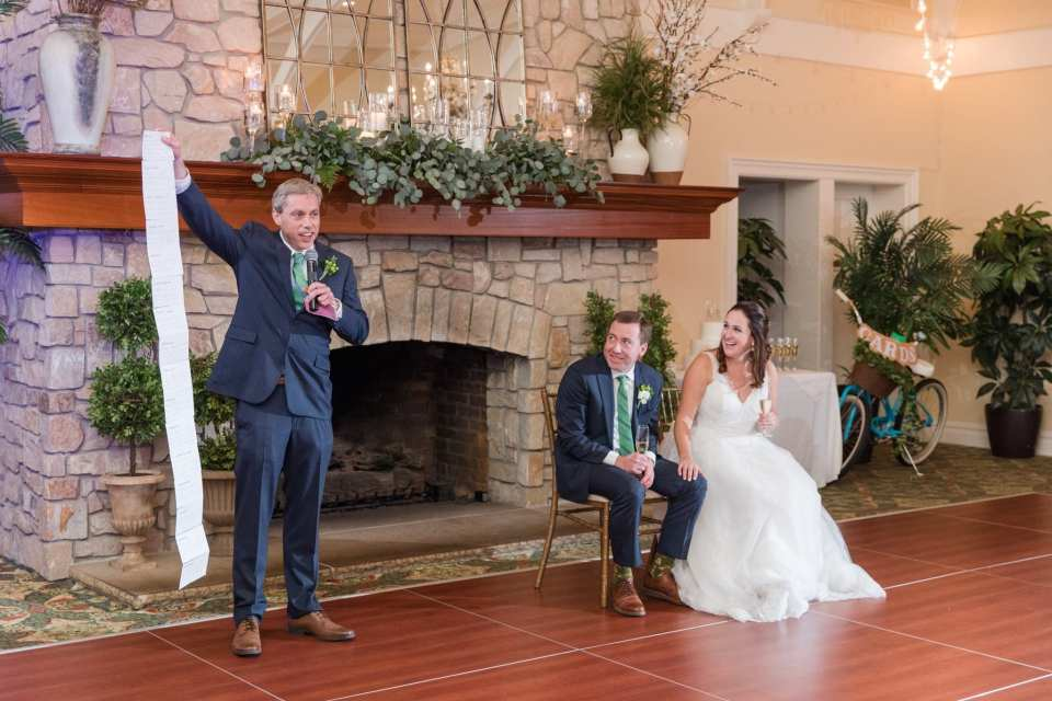 Candid photo of the best man making his speech while the bride and groom look on, laughing while sitting in front of the floor to ceiling stone fireplace at this Spring Lake Golf Club wedding