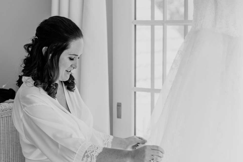 Black and white photo of the bride admiring her hanging gown