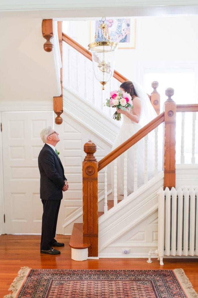 The bride walking down the stairs to have a first look with her father
