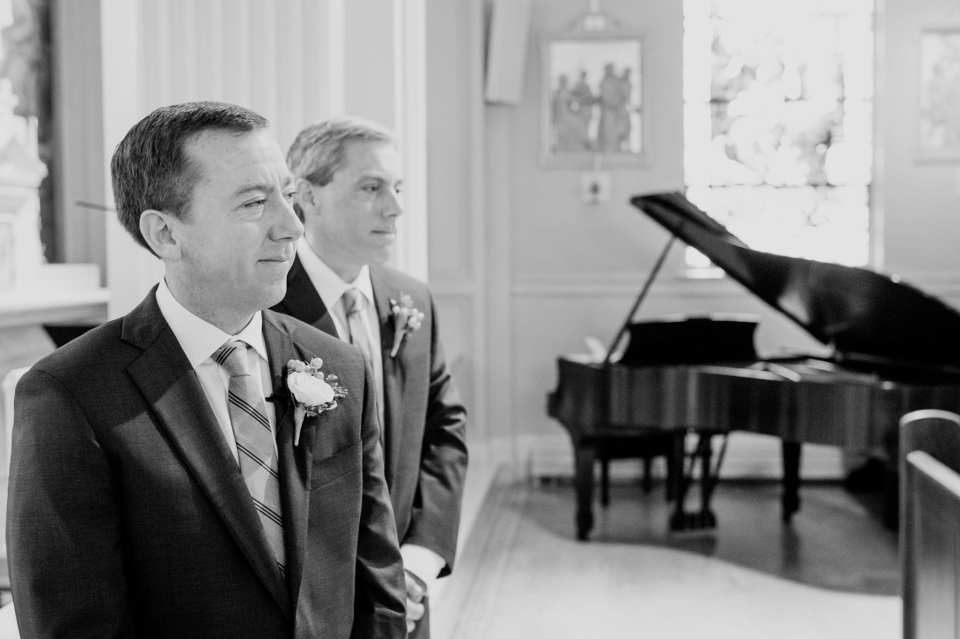 Black and white photo of the groom grinning while watching as his bride walks down the aisle towards him