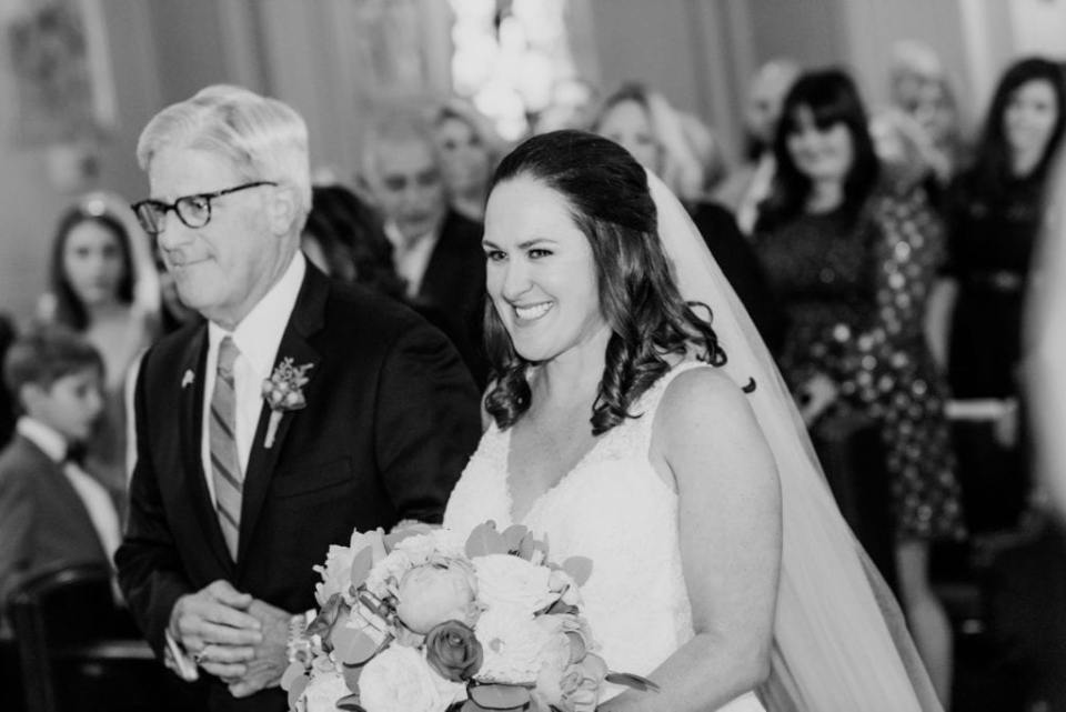 Black and white photo of the bride smiling while being walked down the aisle by her father