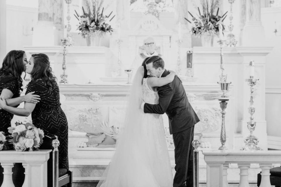 Black and white photo of the bride and groom hugging during their church ceremony