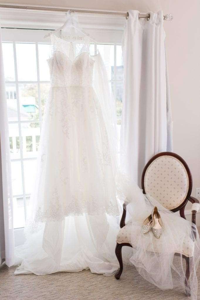 Pronovias gown hanging on display in front of french doors