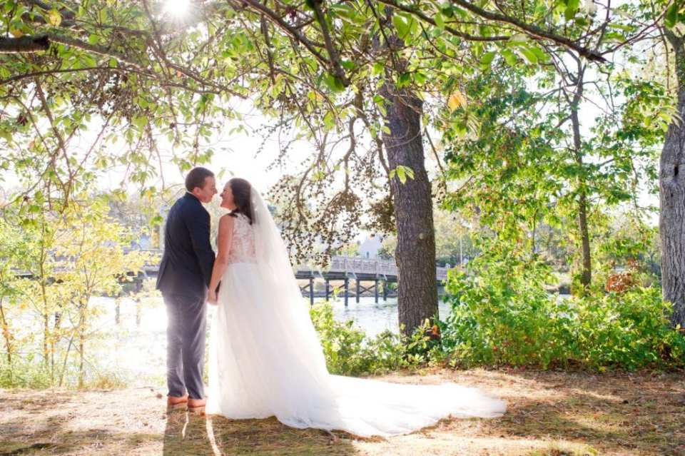 Full length photo of the bride and groom holding hands, facing away from the camera, nose to nose, under tree branches