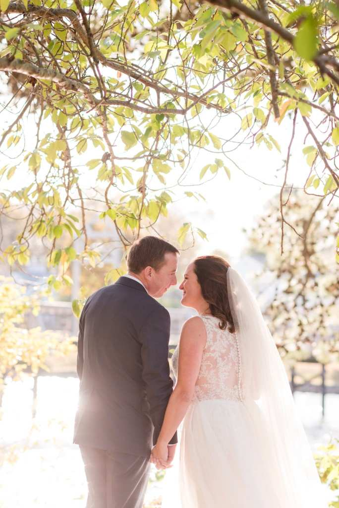 Half shot of the bride and groom holding hands, facing away from the camera, nose to nose, under tree branches