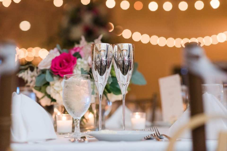Wedding detail photo of the bride and groom's silver toasting flutes on their sweetheart table of their Spring Lake Golf Club wedding