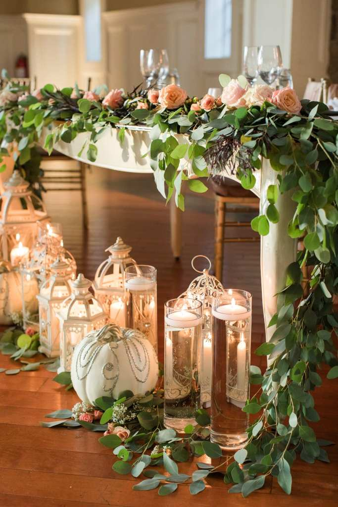 Alternative view of the sweetheart table decorated in greenery and peach roses, lanterns, candles and white pumpkins by the Bloomery Flower Studio in these Ryland Inn Wedding Photos