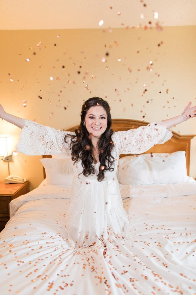 The bride playing in confetti while getting ready in a cutom lace robe by BHLDN