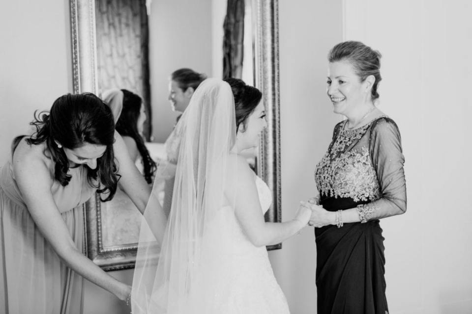 Black and white candid photo of the bride being helped into her wedding gown by a member of her bridal party while holding hands with her mother, smiling in these Ryland Inn wedding photos