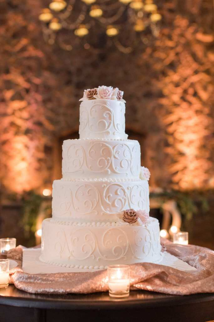 Four tier embossed white wedding cake accented with beige and pink roses by Palermo's Bakery