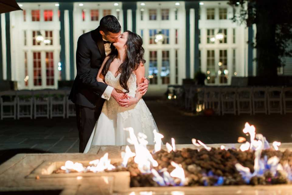 The bride and groom kiss behind a lit firepit outside in these Ryland Inn Wedding Photos