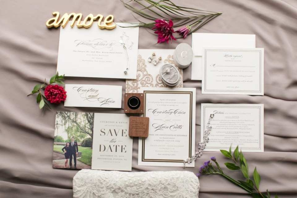 Wedding invitation suite by Minted on display with wedding jewelry and florals