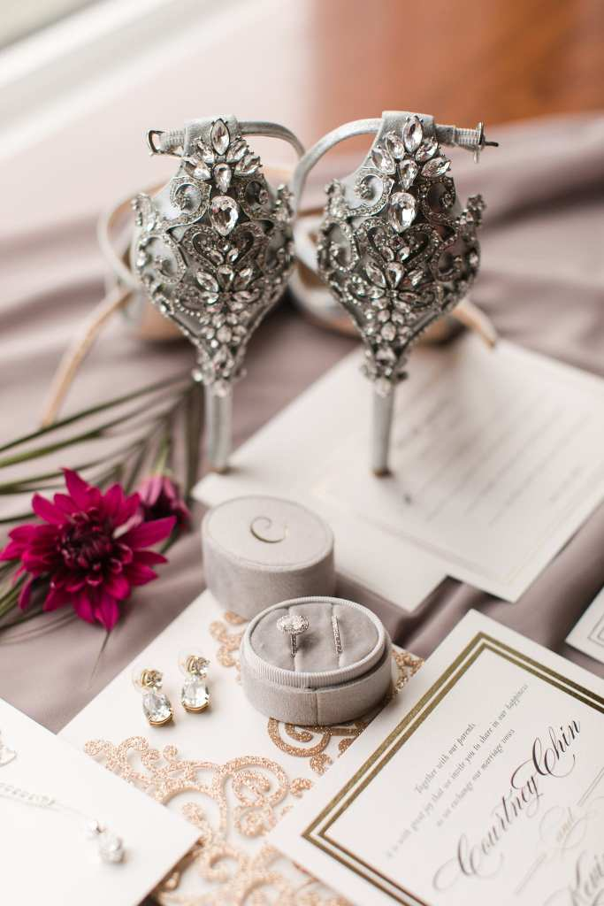 Wedding invitation suite by Minted on display with wedding jewelry and florals and the brides Badgley Mischka shoes