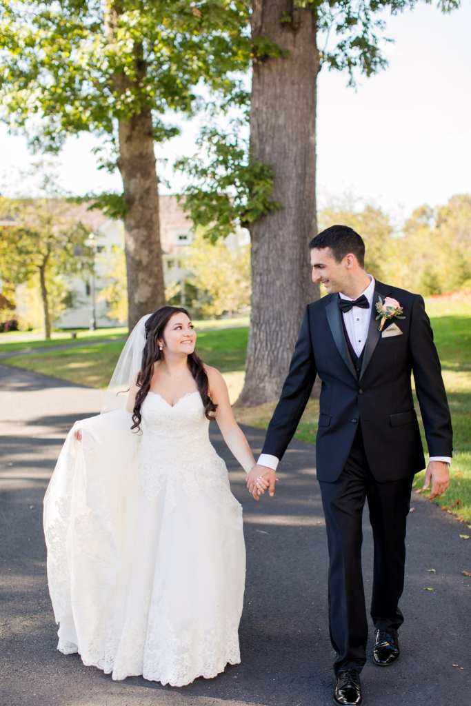 The bride in her Madison James gown walks hand in hand with the groom in his Calvin Klein tuxedo