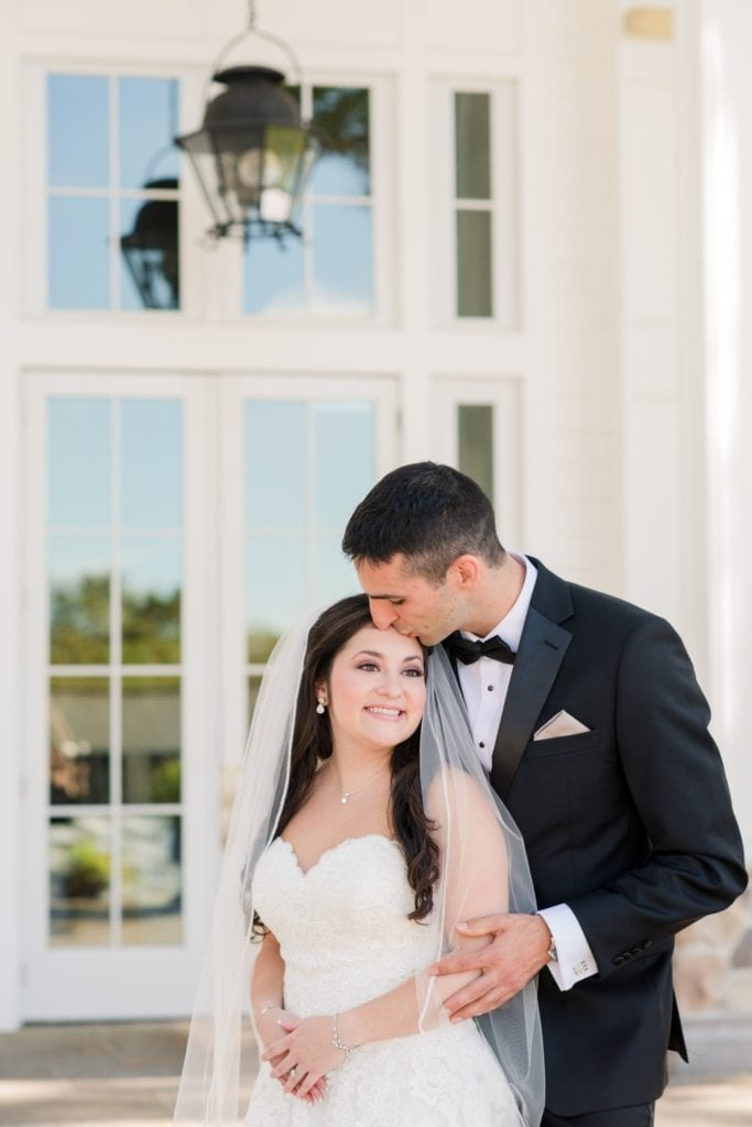 The groom kisses the temple of his bride in these outdoor couple portraits in these Ryland Inn Wedding Photos
