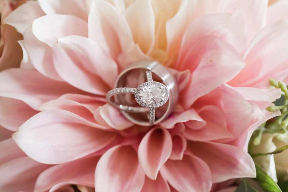 The brides oval diamond engagement ring with diamond halo displayed with the grooms brushed titanium wedding band and brides diamond eternity wedding band by Gabriel & Co set on a peach rose