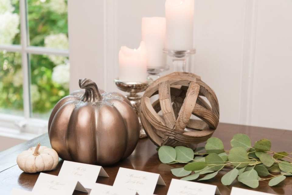 Wedding details of candles and pumpkins in gilded bronze and cream on display on the escort card table