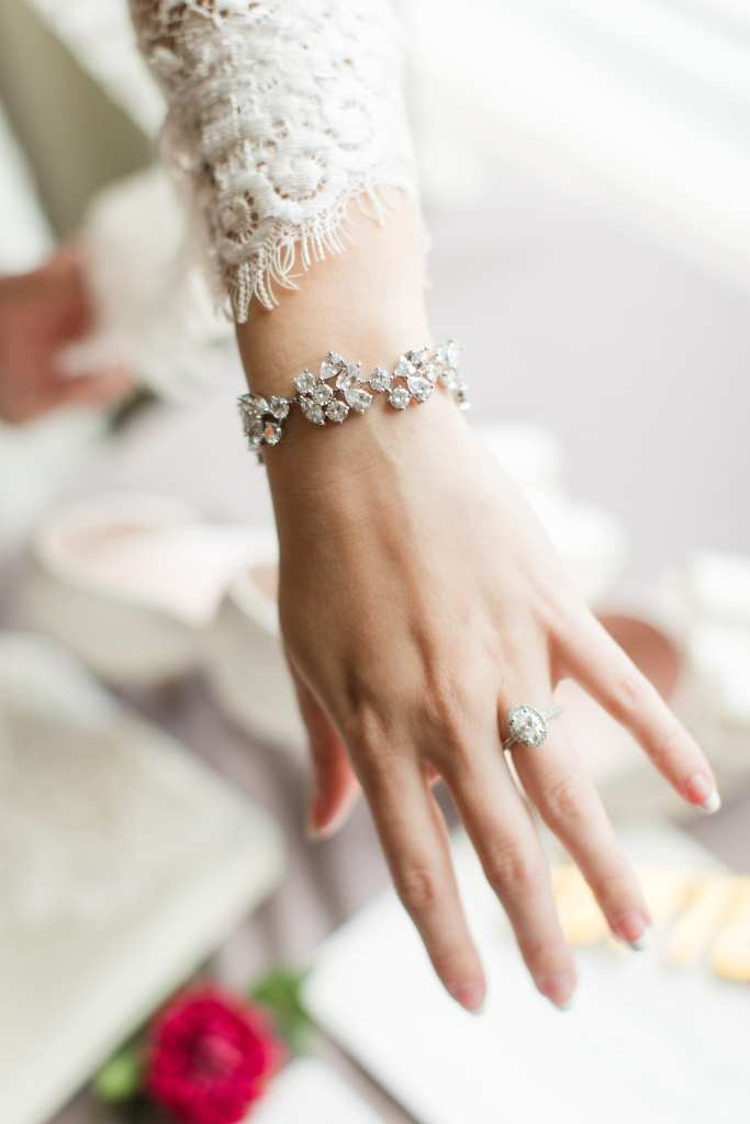The bride showing off her oval diamond engagement ring with diamond halo along with her Kate Spade NY bracelet