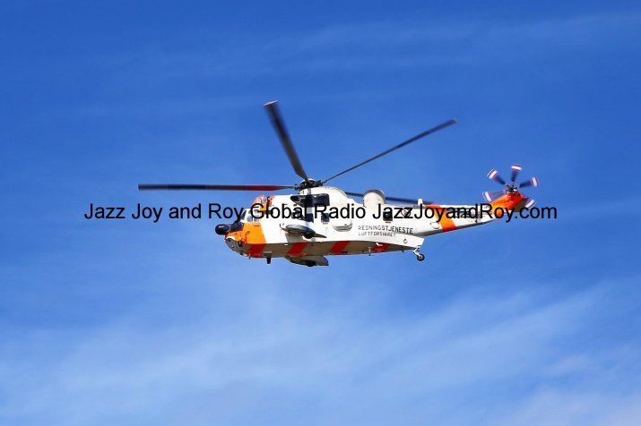 orange and white helicopter flying under blue sky during daytime