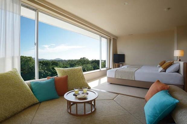 リゾート感を高めてくれる寛ぎの小上がり式ソファを備えた「デラックスルーム」は、木の家具やナチュラルな色合いに癒される 46.8㎡の空間が確保され、大きな窓とその向こうにNEMUの森の緑が広がる絶景を独り占め