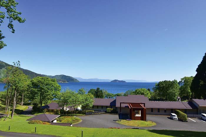 緑豊かな山を背に、琵琶湖を望む絶景のロケーションにお客様をお迎えしている 写真は「絶景の見晴らしの丘」から眺めるホテルと琵琶湖 視線の先には竹生島も見える 他では味わえない希少な景観の中で、非日常の時間をゆっくりと味わっていただける