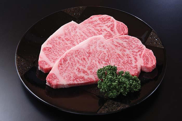 写真上は約1cmのスタンダードな厚さにカットした「サーロインステーキ」。美しい色合いと網目状のサシがやわらかな肉質を物語る。1枚5,400円(税込・約200g)。写真下は厳選された飛騨牛が並ぶ店内の様子
