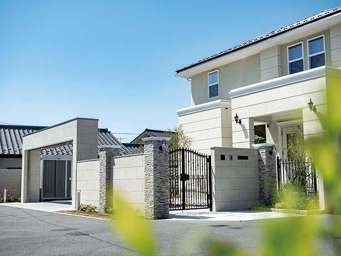 タイルと天然石をふんだんに使ったクローズスタイルの門まわり。鋳物フェンスとグリーンの透け感が「重さ」を和らげ、奥行感を演出。ハイグレードな住宅の外観にフィットした仕上がりになっている
