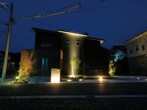 上のお宅の玄関側。ポイントとなる場所に照明を備え、屋根まで光が届くライトが印象的。エクステリアには光の演出も必須であることがよくわかる施工例である