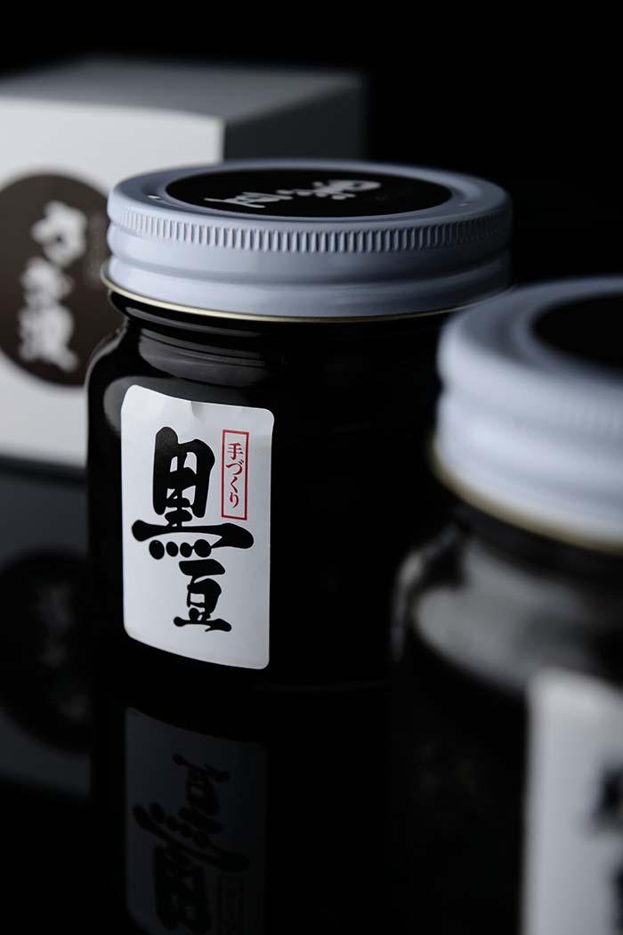 黒豆は、味の良さで日本一と折紙つきの丹波ささやま特産の黒豆の中から選りすぐりを使い、一粒一粒を独自の調理法で色艶、風味を活かして 煮上げた逸品。簡潔なラベルにも名店の品格が漂う 2,000円(税別)