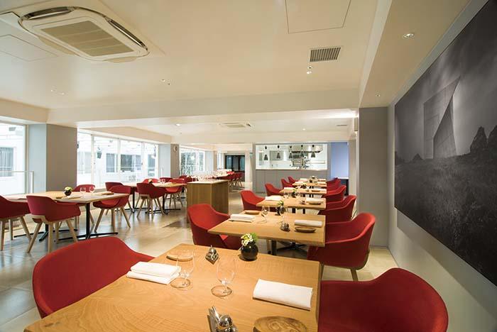 ダイニングはオープンキッチンを望む美食の空間。白を基調に赤い椅子が配されたモダンな空間に心も華やぐ