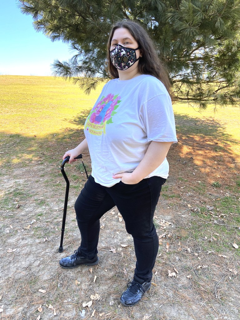 "A photo of Jessi outdoors, wearing a ""Ban Billionaires, Not Inhalers"" shirt they designed, smiling at the viewer from behind their unicorn Vogmask, standing with their cane in one hand and their other hand in their pocket, proudly and visibly disabled. The shirt's colors are vibrant, and the shirt fits well and slightly loose, without being or looking too baggy, ending just past Jessi's butt. A white tank top's straps are just barely visible under the shirt."
