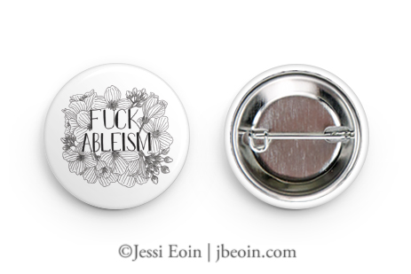 """An image of a white pinback button with a black illustration of flowers and text that reads """"Fuck Ableism"""" in all caps."""