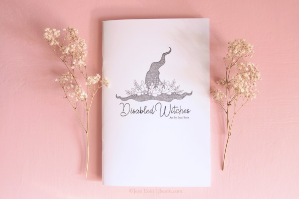 A styled photo of the Disabled Witches art book on a pink background with dried baby's breath on either side. It is a small white book with black text and illustration of a botanical decorated witch hat.