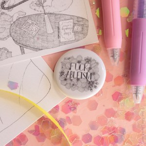 """A photo of the black and white Fuck Ableism button on a festive pink background surrounded by glitter, pens, ribbon, and art prints. The button's design is a floral illustration surrounding a hand lettered font reading, """"Fuck Ableism"""" in all caps."""