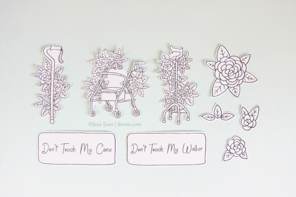 """A photo of the 9 hand cut, die cut stickers from the Canes and Walker sticker set. There are 2 canes and 1 walker, all of which have flowers blooming around them with leaves. There are two rectangular stickers, saying """"Don't Touch My Cane"""" and """"Don't Touch My Walker,"""" as well as three smaller flower stickers and one leaf sticker."""