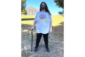 A final full length photo of Jessi modeling the shirt outdoors, standing proudly visibly disabled with their cane and Vogmask and directly facing the viewer with their hair flowing down their shoulder. The shirt's length reaches just past their fingertips with their arm rested naturally at their side.