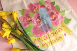 """A photo of a pale beige, cotton tote bag with a bunch of bright yellow daffodils tossed slightly over it. The art on the bag shows a colorful floral design behind a blue and purple inhaler that has the label """"Albuterol Sulfate HFA Inhalation Aerosol"""" and the expiration date """"Aug 20"""" on it. The floral design shows several big, pink peonies with yellow stamens and bright green leaves. Underneath the design is a yellow banner with pink text on it that reads, """"Ban Billionaires, Not Inhalers!"""" in all caps and two pink hearts on either side."""