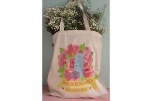 A photo of the tote bag filled with fresh baby's breath flowers and purple wax flowers, propped up against a blue and pink background.