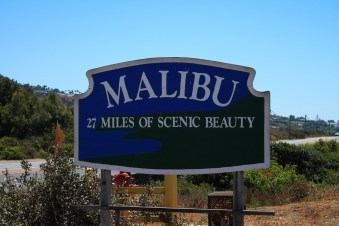 """Malibu, 27 miles of scenic beauty"" written on a big board, plants and a clear sky in the background - one of the most elite LA neighborhoods"