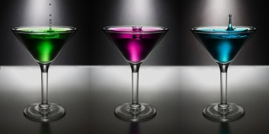 Three martini glasses with different colored drinks and a dark background