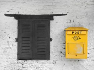 A yellow mailbox next to a brown window.