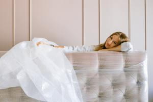 A woman covering her furniture wih bubble wrap