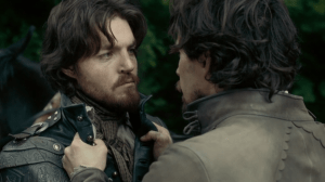 Aramis holds Athos by the lapels, faces close together.