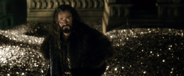 Thorin stands in front of a heap of gold, looking moody.