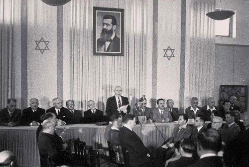 David Ben-Gurion flanked by the members of his provisional government reading the Declaration of Independence at the Tel Aviv Museum, May 14, 1948 (Israel National Photo Collection)